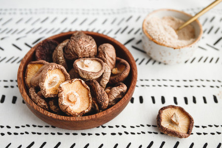 Chinese dried mushrooms Shiitake in a wooden bowl on a table  The concept of medicinal superfoods for health  Top view  flat lay