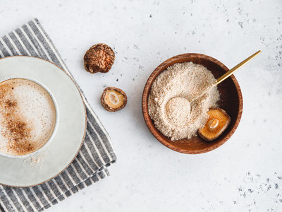 Powder is made from Chinese dried mushrooms Shiitake in a wooden bowl on a table The concept of medicinal additive for healthy food