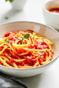Traditional pasta with tomato and Greek basil sauce in a ceramic bowl on a white table