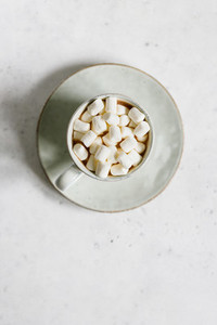 Hot chocolate with marshmallow in a ceramic mug over textured white background  Minimalist style  top view  copy space
