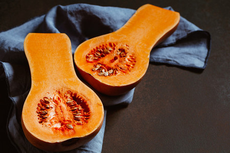 View on raw halves of butternut squash on a kitchen table  Seasonal vegetable food  still life
