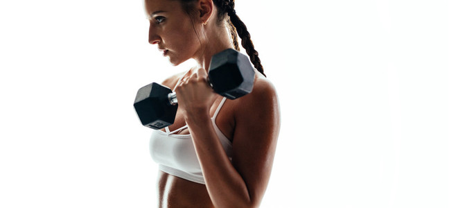 Muscular female exercising with weights