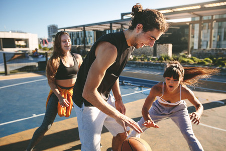 Friends playing basketball game on street court