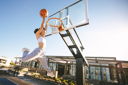 Female playing basketball outdoors