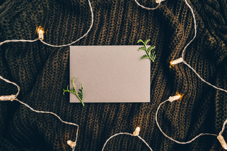 Blank sheet on a warm sweater surrounded festoon lights  Cozy fall or winter mockup for text  Flat lay  top view