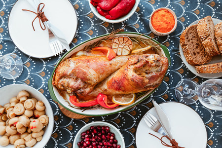 Festive dish for Thanksgiving roasted turkey legs with vegetables on a table with snacks Top view flat lay