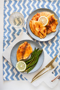Baked tilapia fish with asparagus on a ceramic plate  Healthy mediterranean diet lunch or dinner