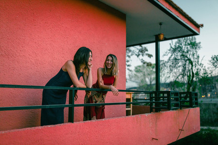 Two young women watch the sunset from their balcony