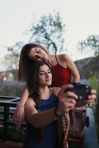 Two young women take a selfie on the balcony
