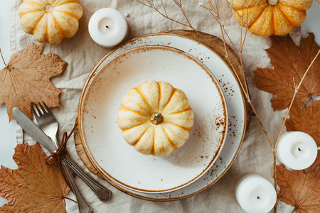 Top view on a decorated table setting for Thanksgiving dinner  Autumn ornate  white pumpkin on ceramic plates