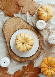Top view of small pumpkin on a plate decorated Autumn ornate  The concept of table setting for Thanksgiving dinner and cooking