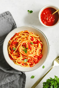 Traditional Italian spaghetti with tomato and Greek basil sauce in a ceramic bowl on a white table