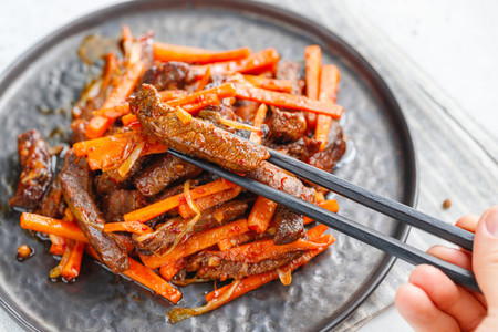 Close up of Chinese spicy Szechuan beef meal on a black plate with wooden sticks over white table