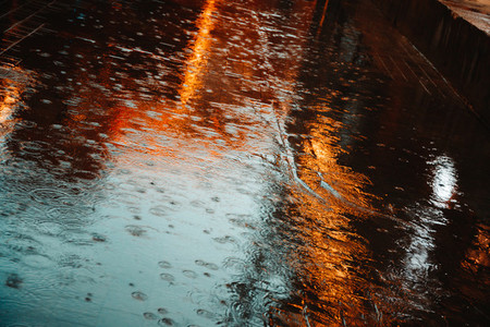 Abstract photography of rain  Raindrops on asphalt in the light of evening lights
