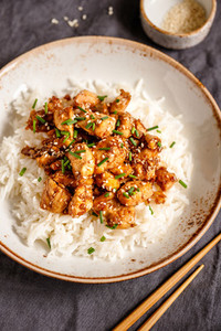 Top view on sesame chicken pieces with rice on a ceramic plate  Chinese traditional dish