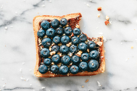Top view of sweet toast with chocolate spread  blueberries and crashed almond on white marble  Flat lay  breakfast concept
