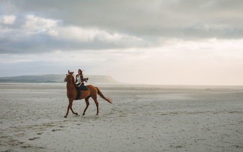 Woman horse riding along the sea shore