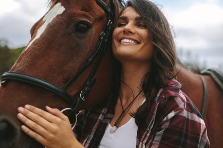 Happy woman hugging her horse