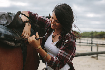 Woman getting her horse ready for a ride