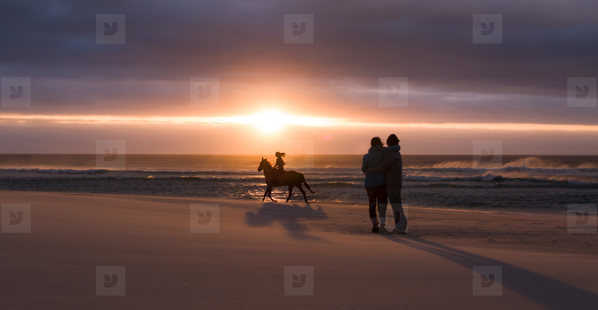 Couple enjoying sunset with woman riding a horse at beach