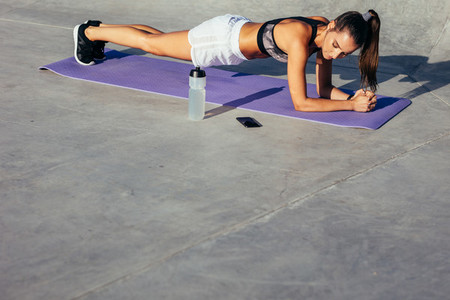 Fitness woman holding a plank pose
