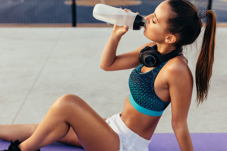 Sportswoman drinking water after workout
