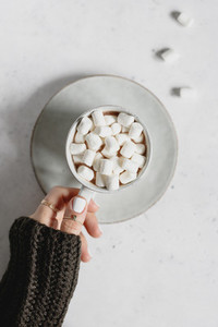 Girls hand holds a cup of hot chocolate with marshmallow over textured white background  Minimalist style  top view  copy space