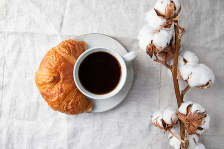 Cup of black coffee with croissant on  table  The concept of breakfast  flat lay  top view