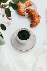 Cup of black coffee with croissant on white  table The concept of breakfast flat lay top view