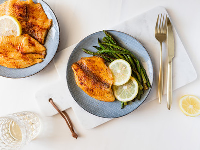 Roasted tilapia fish with asparagus on a ceramic plate Healthy mediterranean diet lunch or dinner Top view flat lay