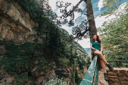 Young woman sitting on a fence observes the forest