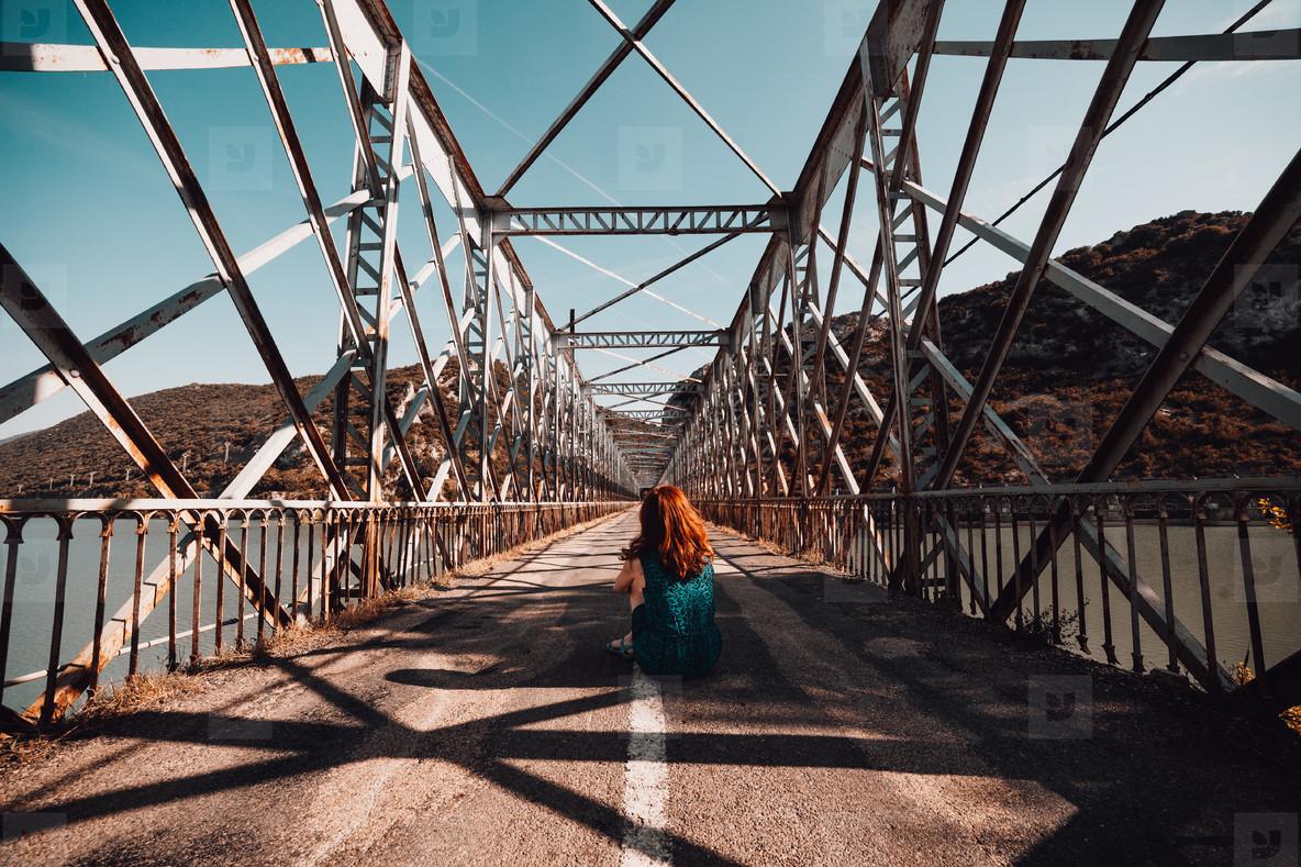 Young redhead woman sitting on an old steel bridge