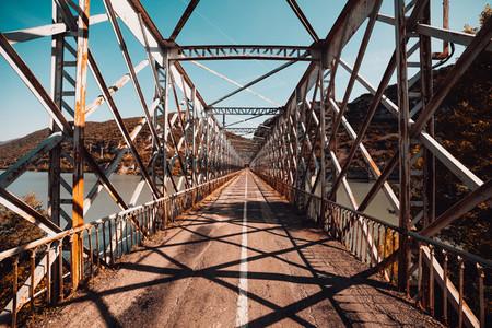 Old steel bridge road over lake in huesca spain
