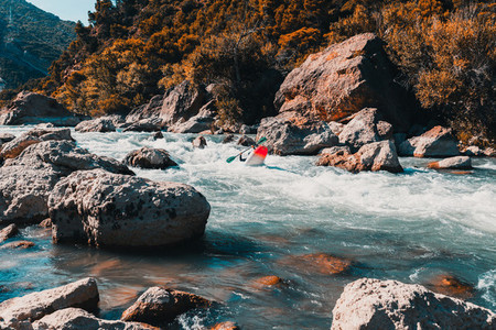 A man practicing rafting with his canoe on a mountain river