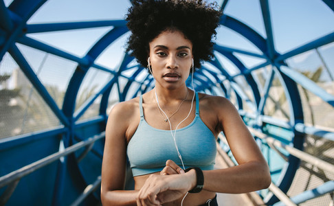 Sportswoman checking pulse on smart watch