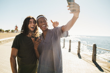 Friends make a selfie on the seaside hangout