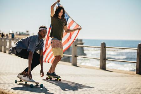 Friends skateboarding on seaside promenade