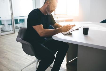 Mature businessman working on his digital tablet