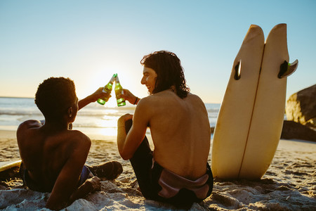 Surfers toasting beers on the beach