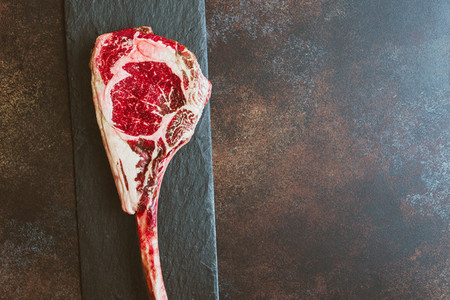 Top view of raw dry aged marble beef steak Tomahawk Flat lay copy space cooking concept