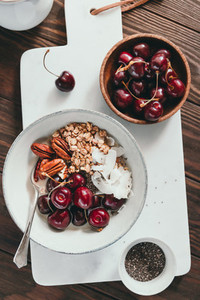 Healthy summer vegetarian breakfast with granola cherry pecans coconut flakes chia and oat milk on marble tray