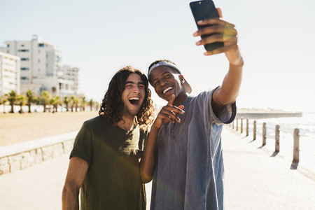 Friends making a selfie by seaside promenade