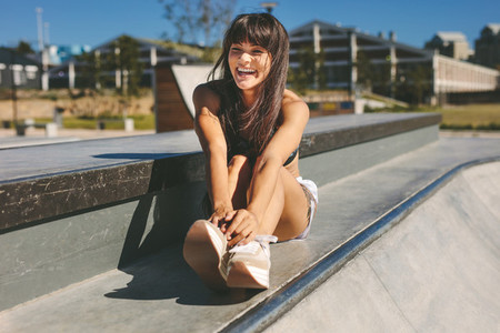 Smiling young woman sitting at skate park