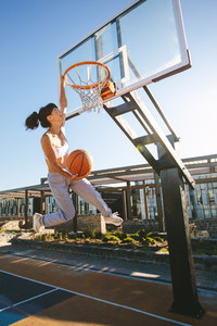 Street basket player making slam dunk