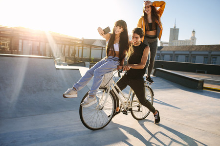 Woman taking selfie with friends on bicycle
