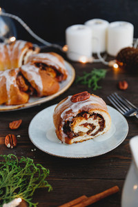 Piece of Swedish tea ring Christmas cake with cinnamon  pecans and raisins on a warm knitted sweater  The concept of cozy winter Holidays and homemade bakery