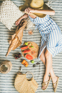 Summer picnic setting with wine in womans hands baguette fruits