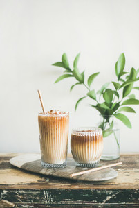 Iced coffee drink in tall glasses with milk and straws