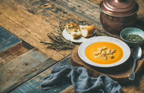 Warming pumpkin cream soup with croutons and seeds  wooden background