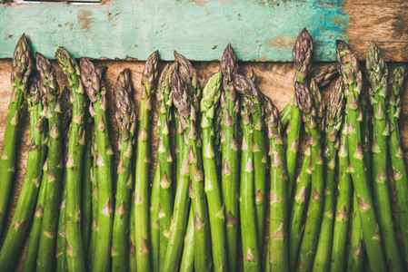 Raw uncooked green asparagus over rustic wooden tray background close up